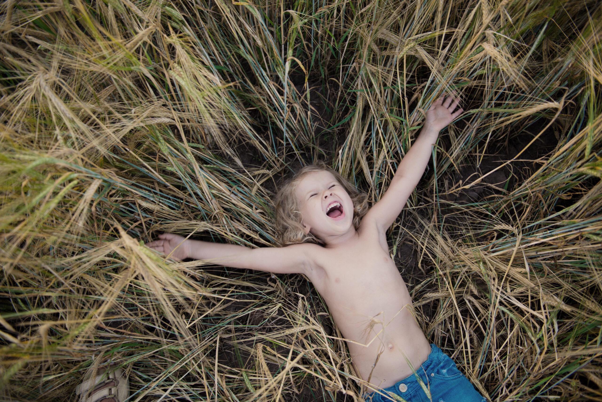 счастливый ребенок лежит в поле
